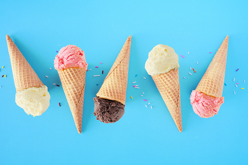 Ice cream cone flat lay over a blue background. White vanilla, pink strawberry and dark chocolate flavors.