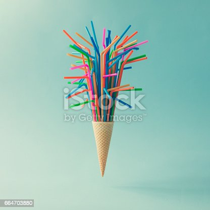 istock Ice cream cone with colorful drinking straws on bright blue background. Minimal food concept. 664703880