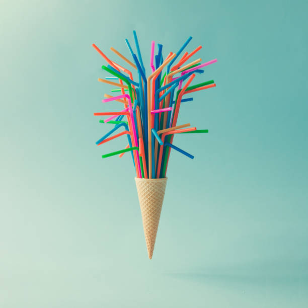 Ice cream cone with colorful drinking straws on bright blue background. Minimal food concept. stock photo