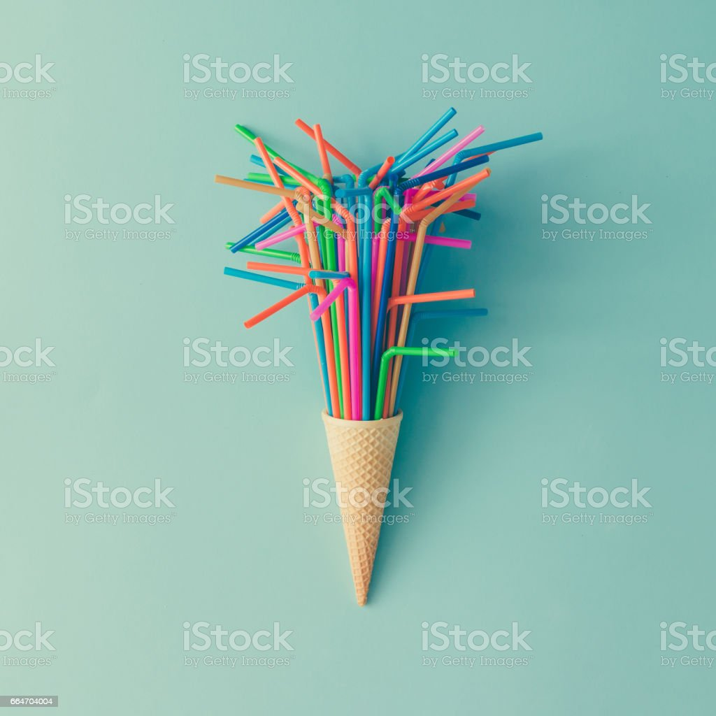 Ice cream cone with colorful drinking straws on bright blue background. Minimal food concept. Flat lay. stock photo