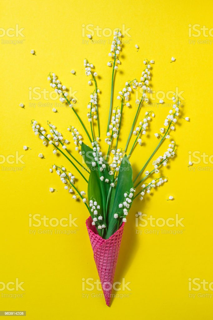 Ice cream cone with lily of the valley flowers on a yellow background. Minimal spring concept. Flat lay - Royalty-free Anniversary Stock Photo