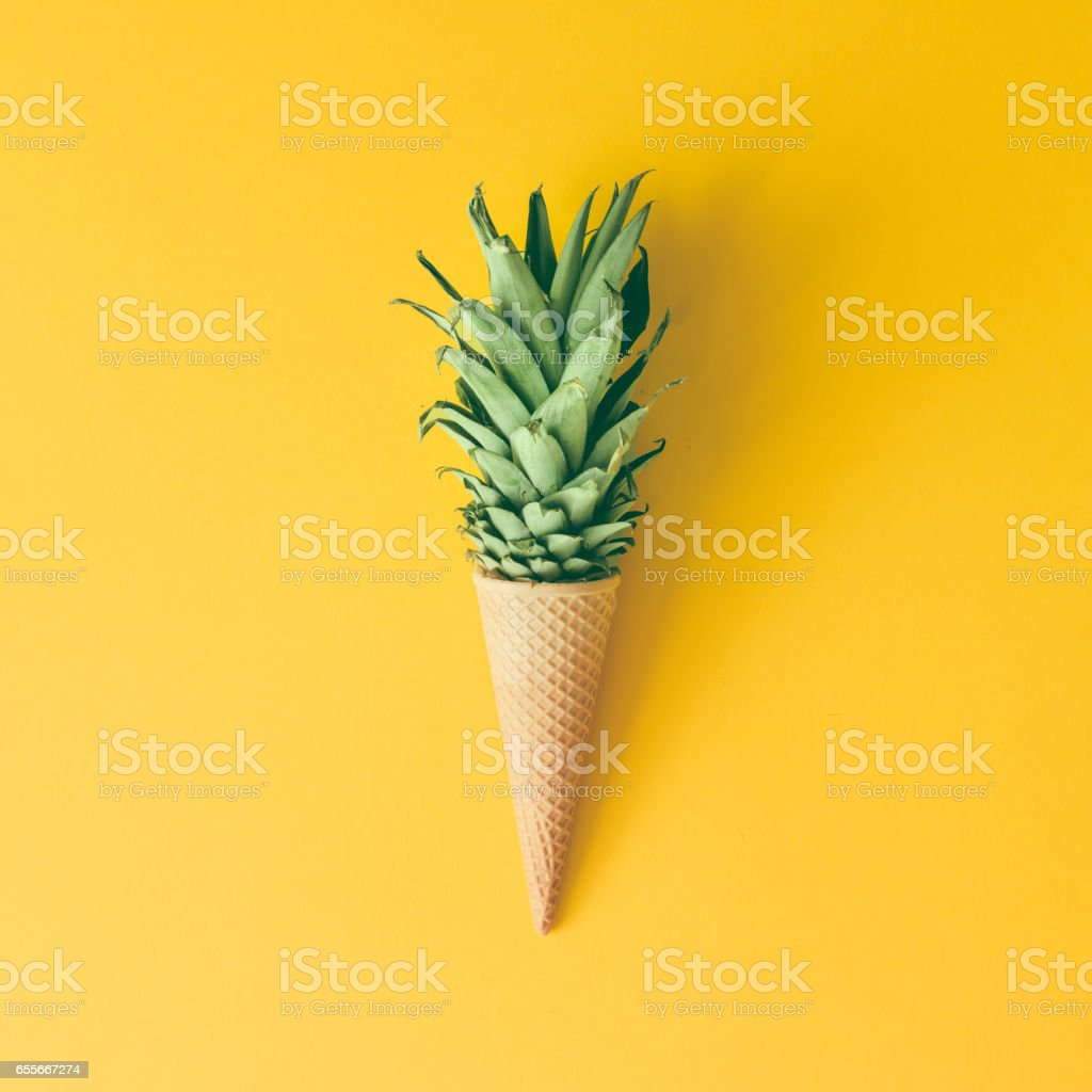 Ice cream cone with pineapple leaves on bright yellow background. Fruit and candy concept. Flat lay. - Стоковые фото Абстрактный роялти-фри