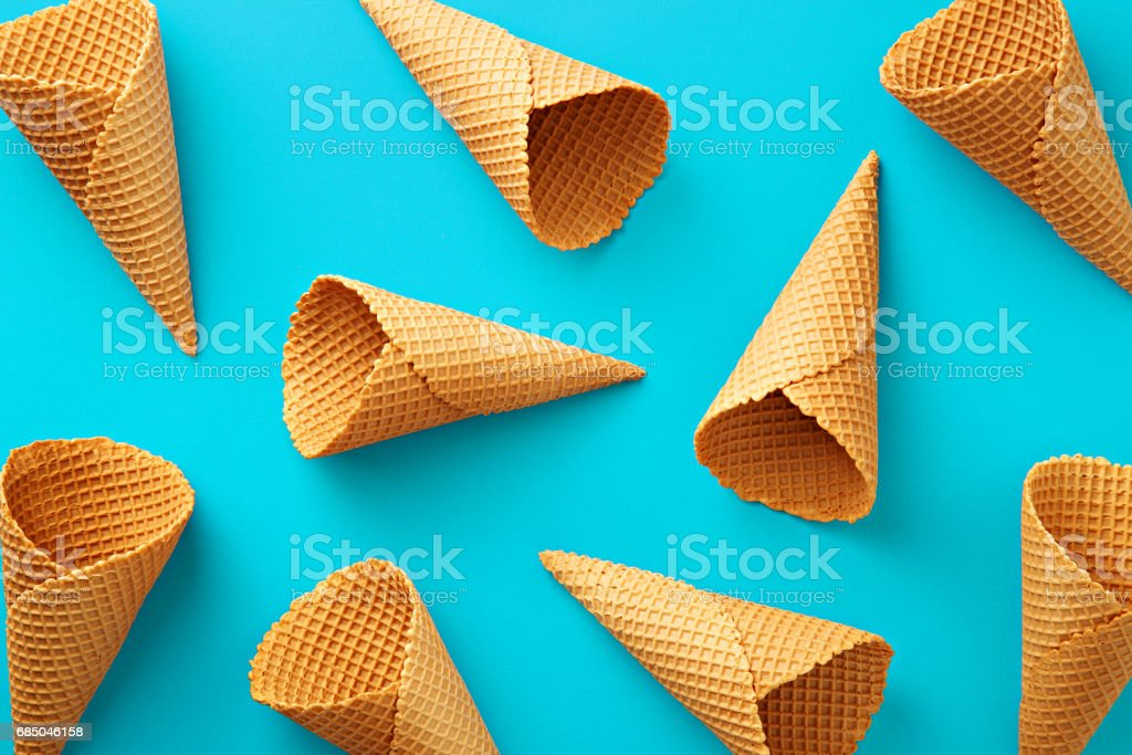 Ice cream cones pattern. Turquoise background. Sweet, summer and empty concept. Top view. Flat lay stock photo