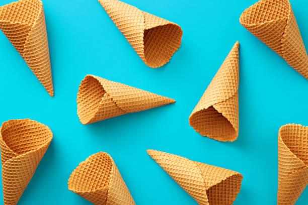 eiscreme-kegel-muster. türkisfarbenen hintergrund. sweet, sommer und leerer begriff. ansicht von oben. flach zu legen - eiswaffeln stock-fotos und bilder
