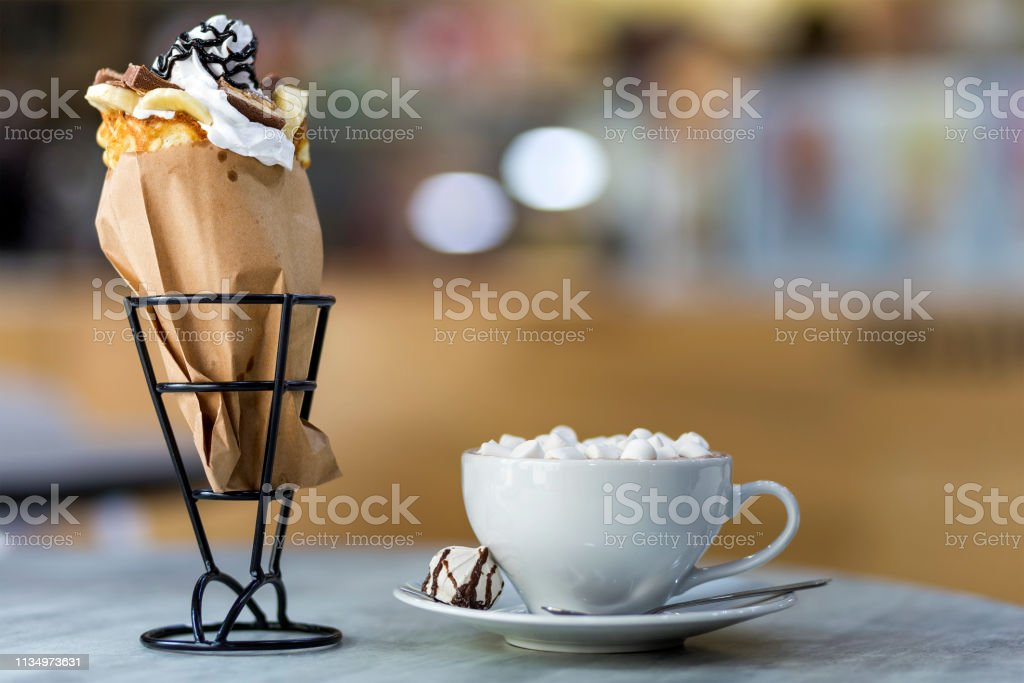 Ice cream dessert in wafer cup with chocolate cookies and and mug of...