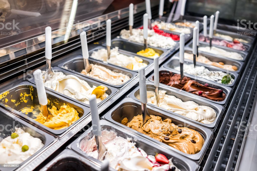 Ice cream frozen yogurt colorful serving counter parlour with many scoopable flavors, sorbet, chocolate, toppings, coffee stock photo