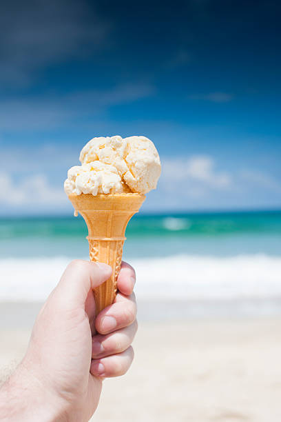 ice cream on sunny beach in st. ives cornwall - ice cream cone stock photos and pictures