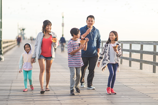 An attractive Filipino couple and their three children eat ice cream cones as they walk down a California boardwalk by the beach