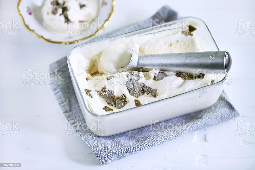 Ice cream scoop in ice box with salty caramel ice cream and truffles stock photo