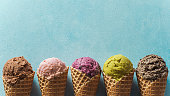 istock ice cream scoops in cones with copy space on blue 1155591668