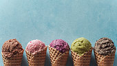 istock ice cream scoops in cones with copy space on blue 1159197374