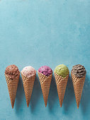 istock ice cream scoops in cones with copy space on blue 1159197383