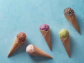 istock ice cream scoops in cones with copy space on blue 1159197390