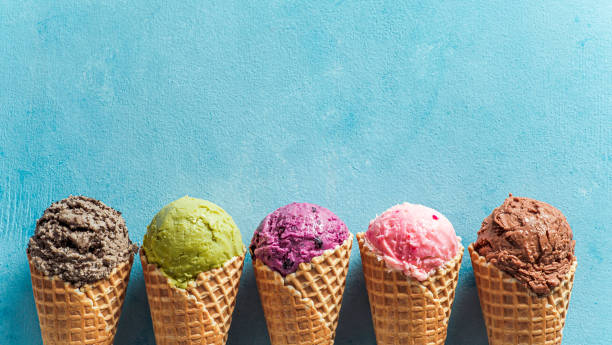 ice cream scoops in cones with copy space on blue Various ice cream scoops in cones with copy space. Colorful ice cream in cones chocolate, strawberry, blueberry, pistachio or matcha, biscuits chocolate sandwich cookies on blue background. Top view ice cream stock pictures, royalty-free photos & images