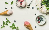 istock Ice cream scoops, peonies and berries over white background 912137744