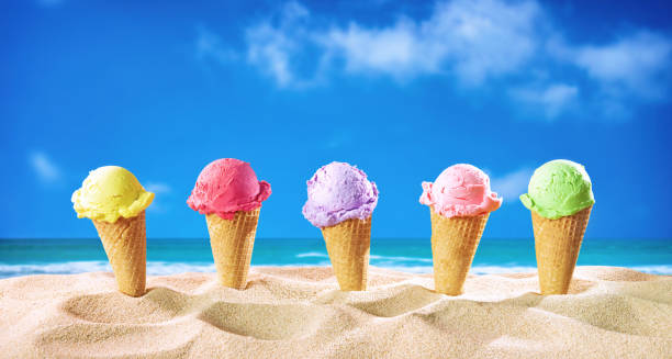 Ice creams cones and seashells in the sand on the beach stock photo