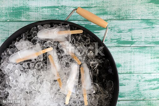 Ice crushed on green wooden background and ice in a black tray.
