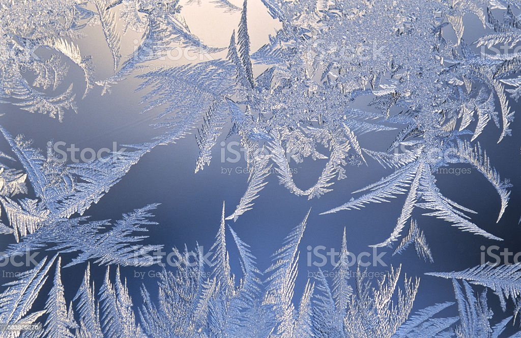 Ice crystals on window glass stock photo