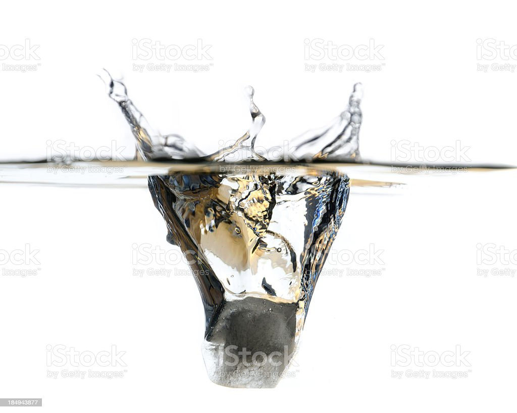 Ice cube falling in water stock photo