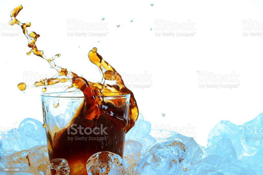 Cubo de Gelo caindo em um copo de refrigerante - foto de acervo