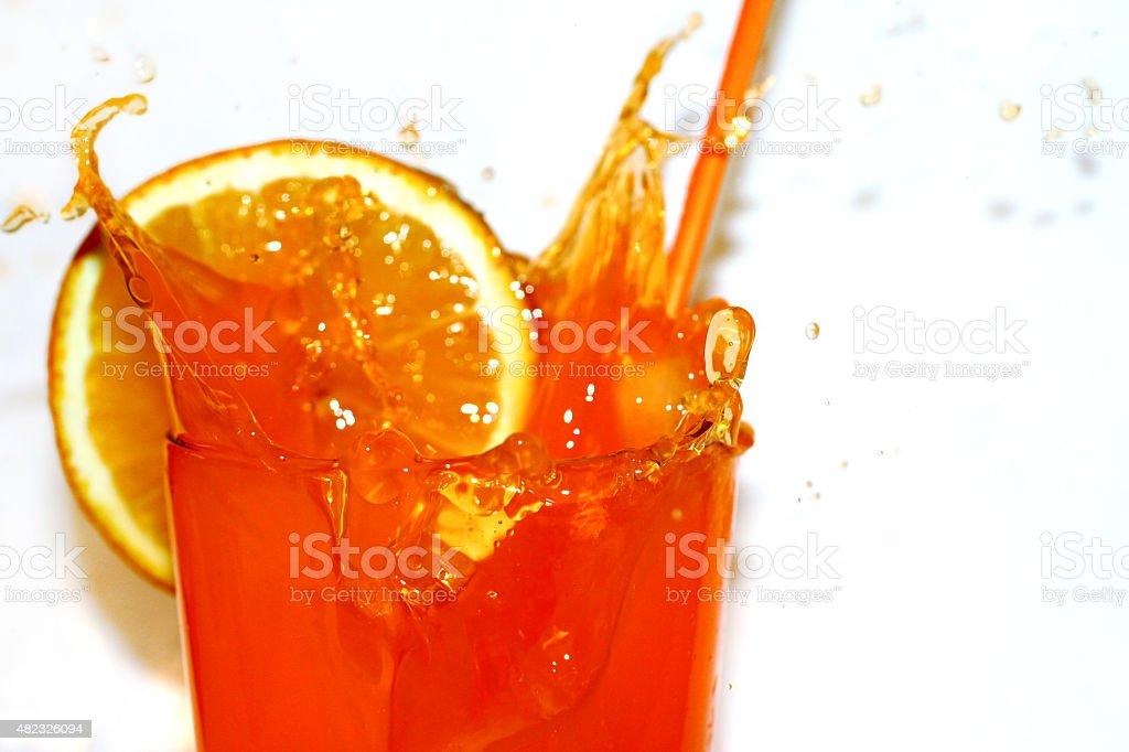Cubo de Gelo caindo em um copo de suco de laranja - foto de acervo