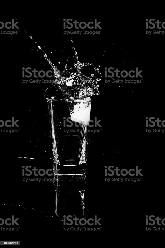 Ice cube splashing into a water glass royalty-free stock photo