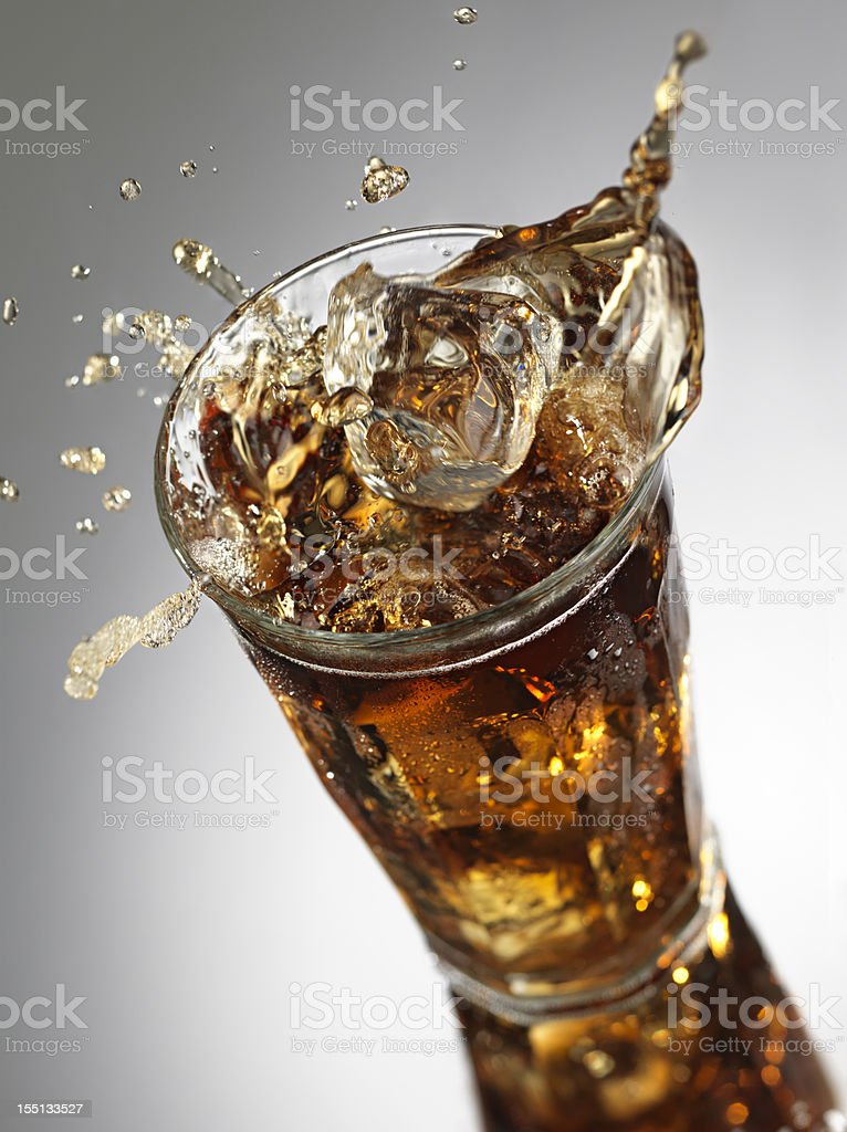 Ice Cube splashing into Cola royalty-free stock photo
