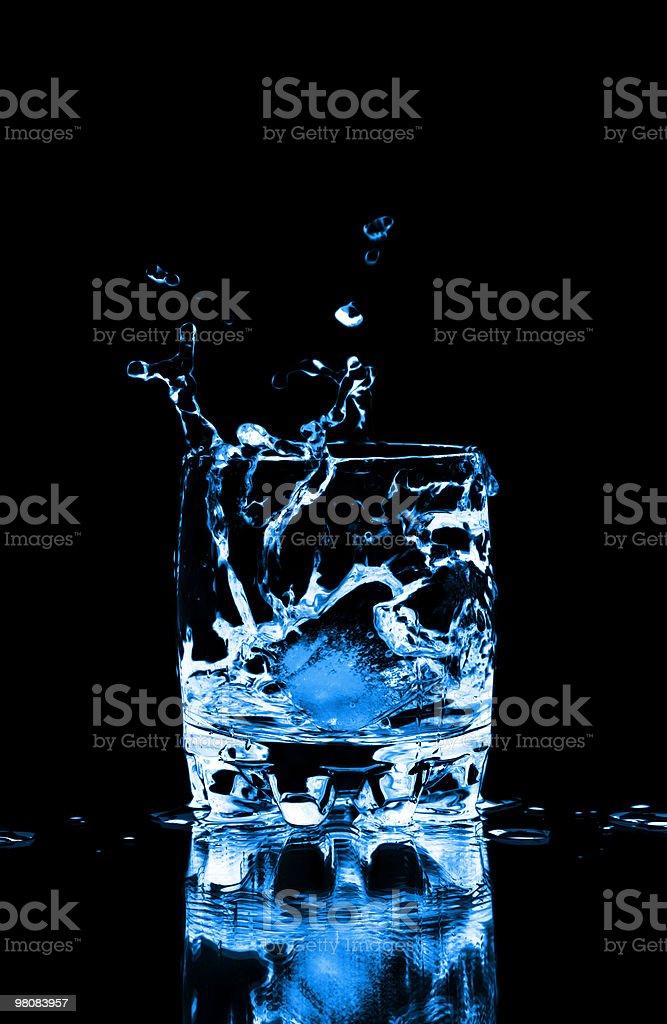 Cubo di ghiaccio spruzzi in un bicchiere di acqua foto stock royalty-free
