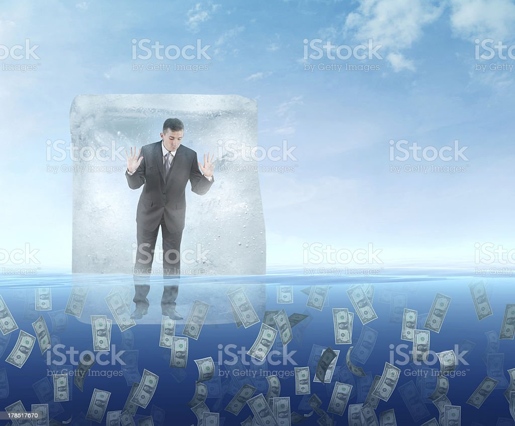 Ice cube with a businessman floating in the sea stock photo