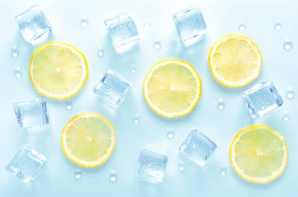 Eiswürfel und frische Zitronenscheibe mit Wassertropfen auf blauem Hintergrund – Foto