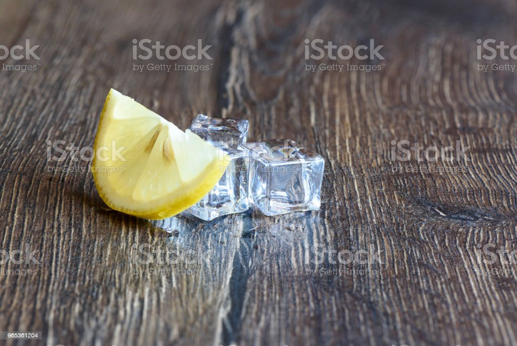 Ice cubes and lemon on a wooden table royalty-free stock photo