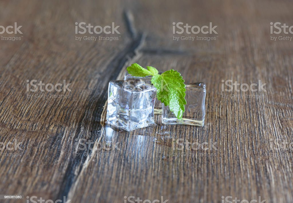 Ice cubes and mint leaves on a wooden background royalty-free stock photo