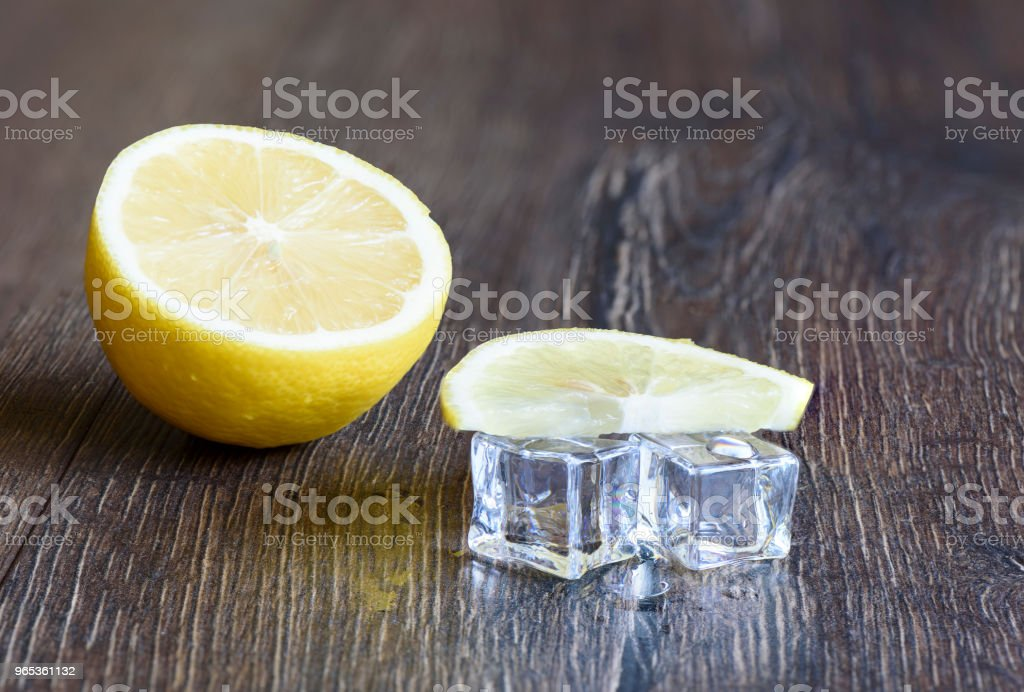 Ice cubes and slice of lemon on a wooden background royalty-free stock photo