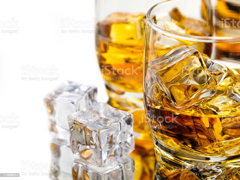 Ice cubes and whiskey on the rocks in glasses royalty-free stock photo