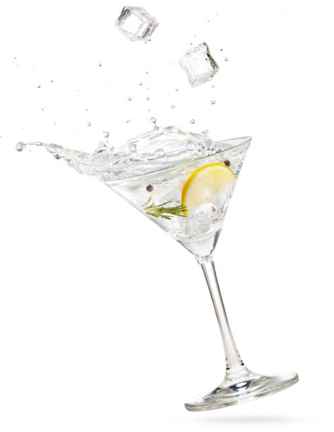 ice cubes falling into a tilted gin martini ice cubes falling into a gin martini cocktail splashing on white background martini stock pictures, royalty-free photos & images