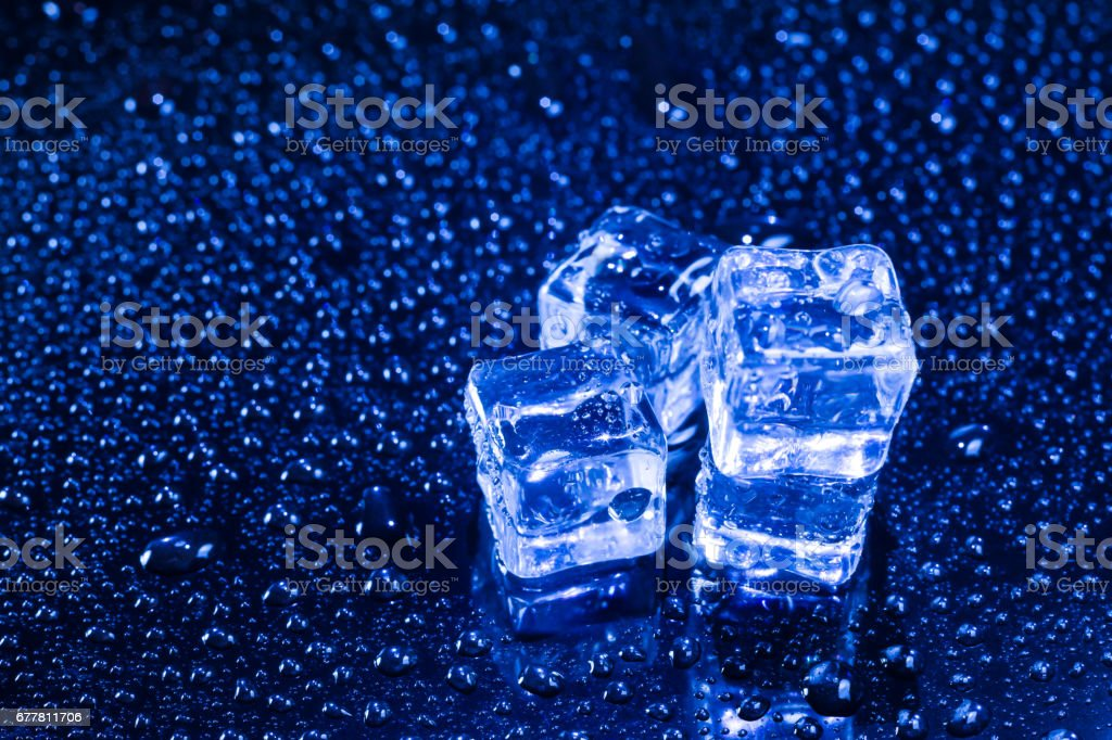 Ice cubes in blue light on black wet table. royalty-free stock photo