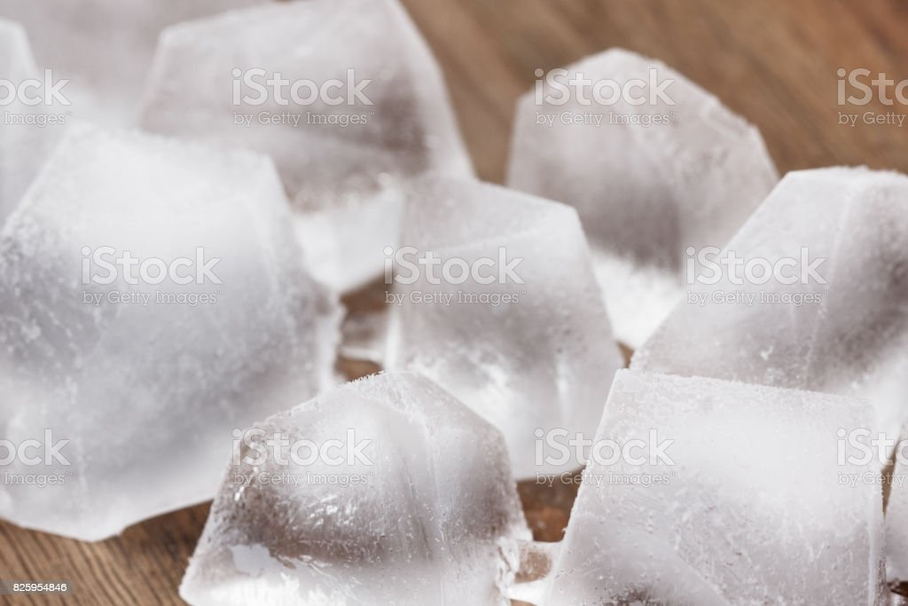 Ice cubes on a wooden background stock photo