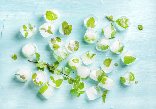 ice cubes with frozen mint leaves inside on blue turquoise background, top view - menta erba aromatica foto e immagini stock