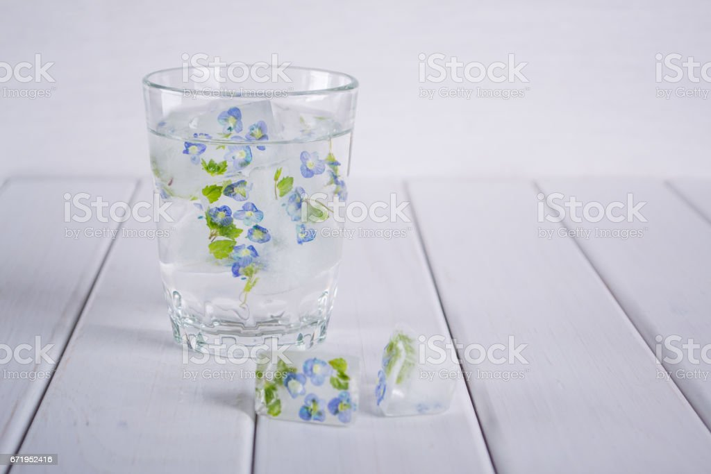 Ice cubs with frozen flowers in glass of water for cosmetic stock photo