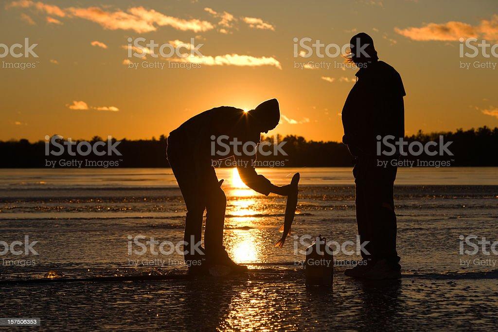Ice fisherman catching fish on frozen lake at sunset. royalty-free stock photo