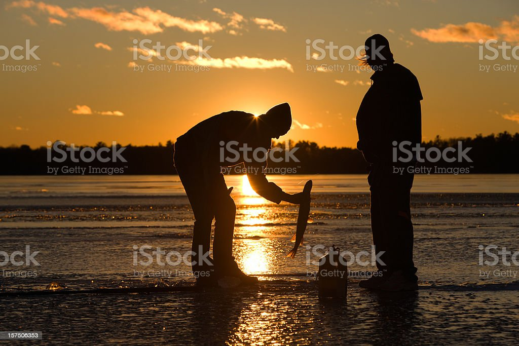 Ice fisherman catching fish on frozen lake at sunset. stock photo