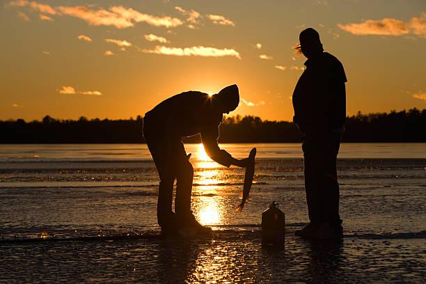Ice fisherman catching fish on frozen lake at sunset. stock photo