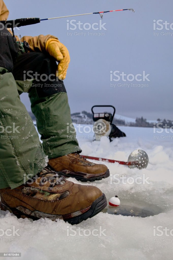 Ice fisherman fishing in ice hole and equipment stock photo