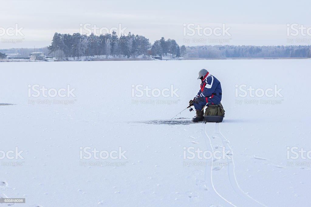 Ice fishing. Fisherman sitting on a frozen lake for fishing stock photo