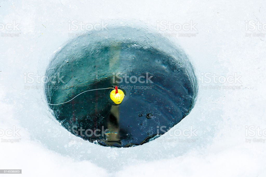 Ice fishing hole with line and bobber tossed in stock photo