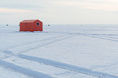 Orange Ice fishing huts on a frozen lake in Ontario at sunset showing tracks