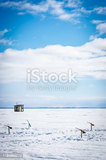 Ice fishing rods above holes in frozen Lake Saint Pierre by the Saint Lawrence River in Quebec with fishing cabin in background.