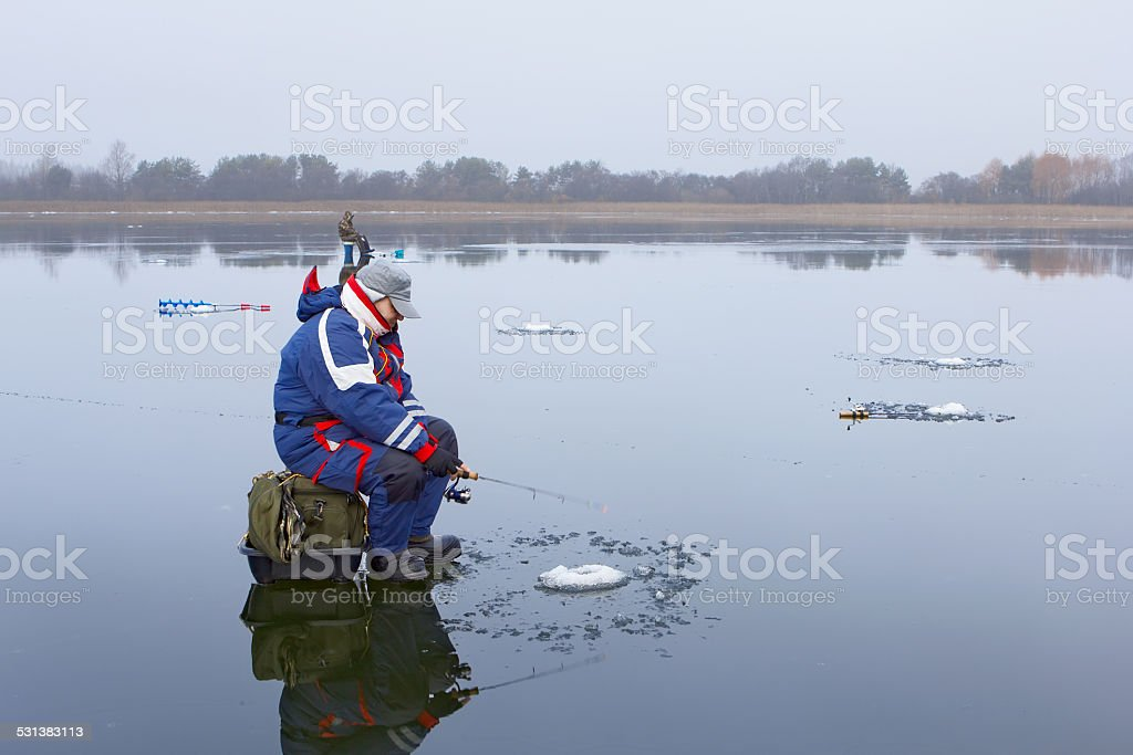 Ice fishing in the thaw stock photo