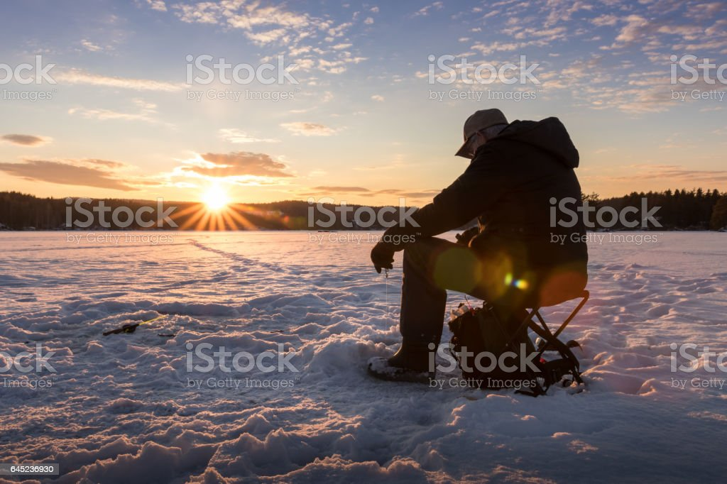Ice fishing on a lake in Norway at sunset. stock photo