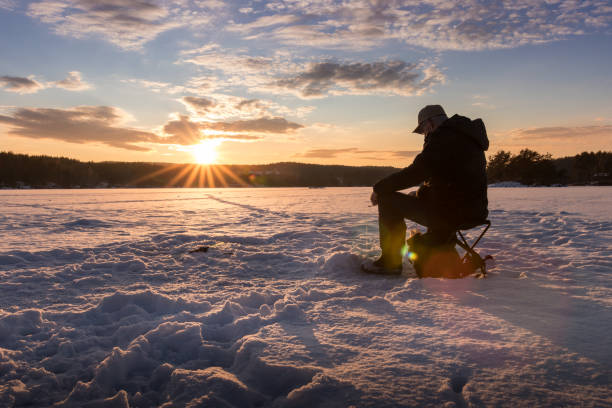 Ice fishing on a lake in Norway at sunset. Ice fishing on a lake in Norway at sunset. perch fish stock pictures, royalty-free photos & images